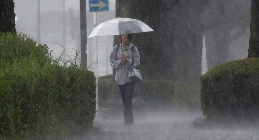 Девушка идет сквозь сильный дождь. Архивное фото
