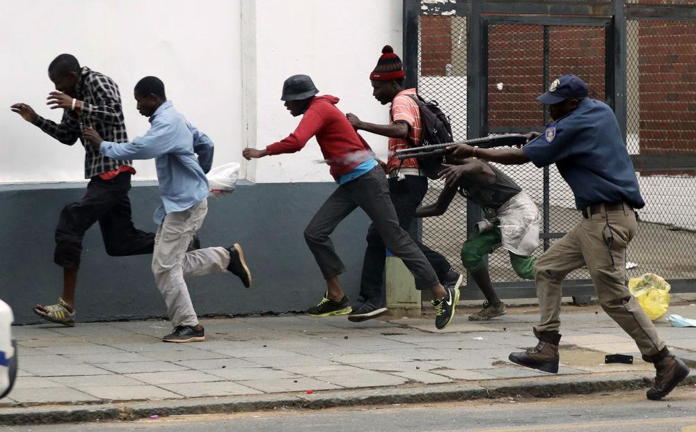 Полицейский разгоняет демонстрантов на антимигрантском митинге в Претории