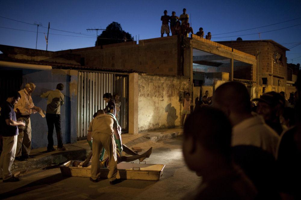 Работники морга забирают тело мужчины, погибшего во время стрельбы в Сальвадоре (Бразилия)