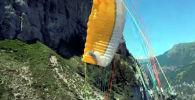 Пролетая между гор, американский экстремал Грег Овертон потерял контроль над парапланом и врезался в скалу.