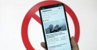 Человек держит смартфон с открытым сайтомBaltnews.lv, принадлежащий МИА Россия сегодня
