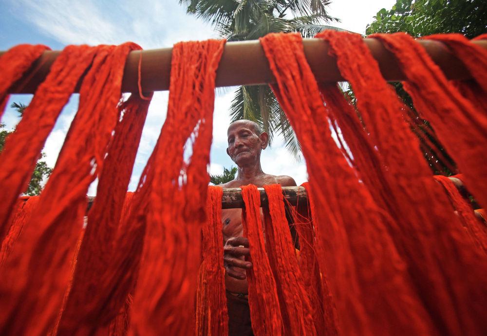 Рабочий текстильной фабрики в Агартале (Индия) вывешивает нити после покраски