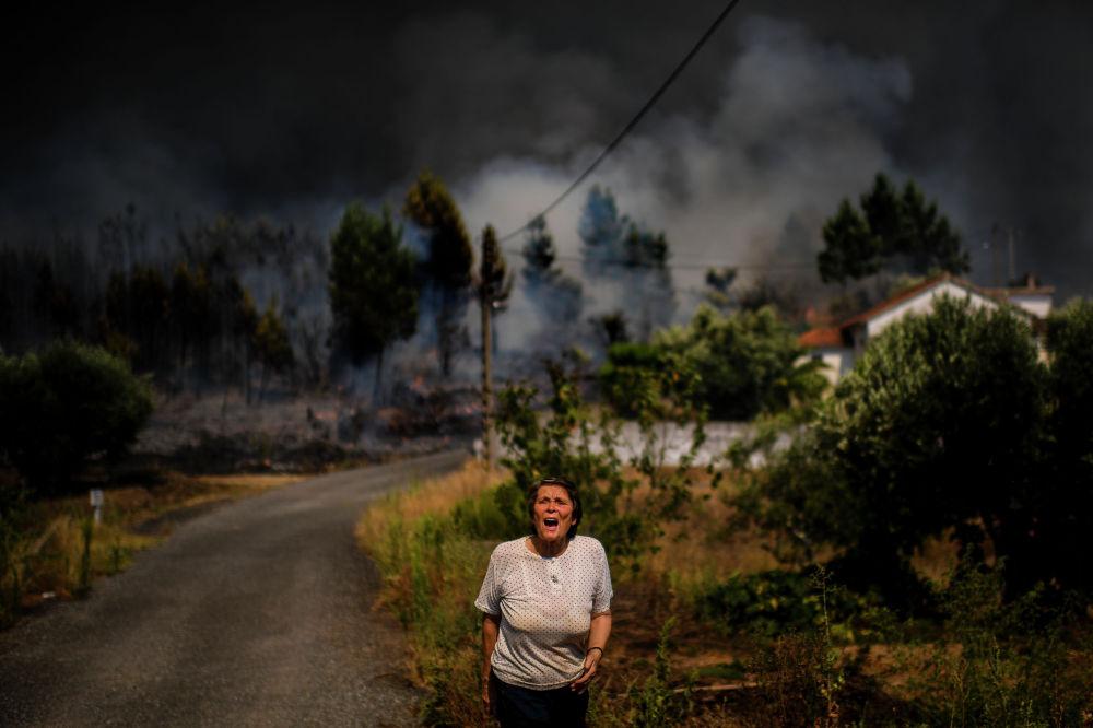 Жительница деревни в Макао, к дому которой подступает лесной пожар, зовет на помощь