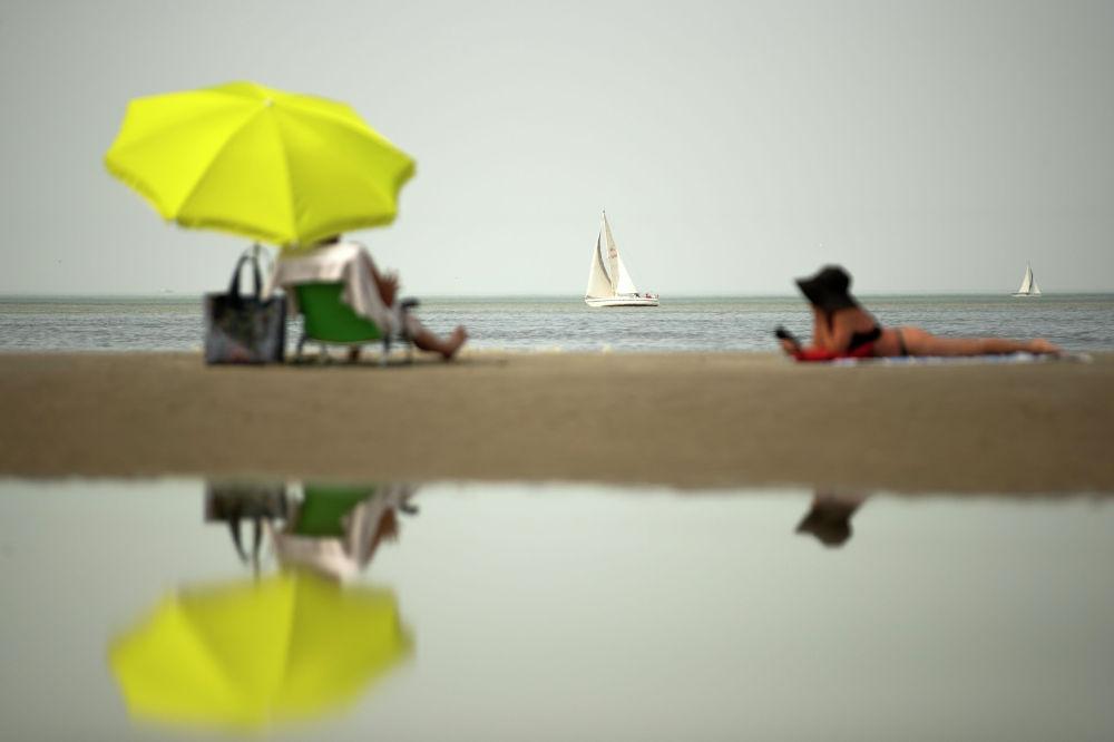 Отдыхающие на берегу моря в бельгийском муниципалитете Де Хаан