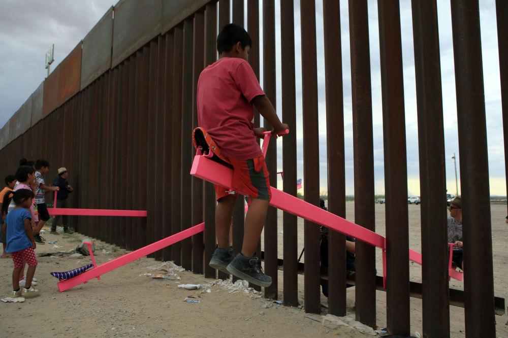Американские и мексиканские дети качаются на качелях на границе Мексики и США. Конструкции сделаны так, что качаться на них могут люди, находящиеся по разные стороны границы.  Необычные качели установили в знак протеста против стены Трампа.