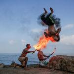 Мужчины показывают трюк с огнем на пляже города Газа (Палестина)
