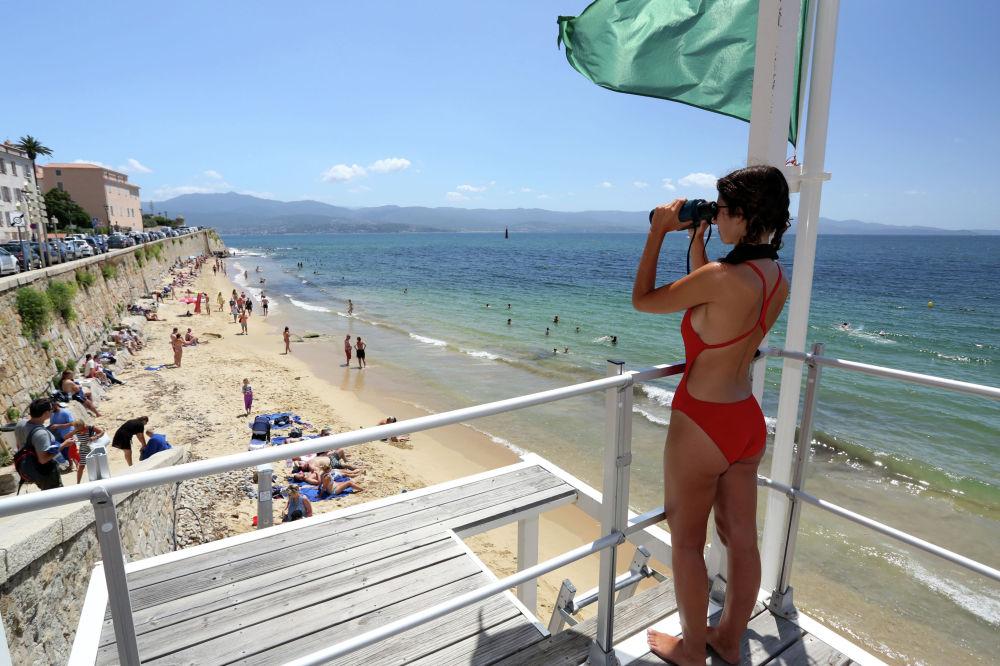 Девушка-спасатель наблюдает за отдыхающими с вышки на Корсике