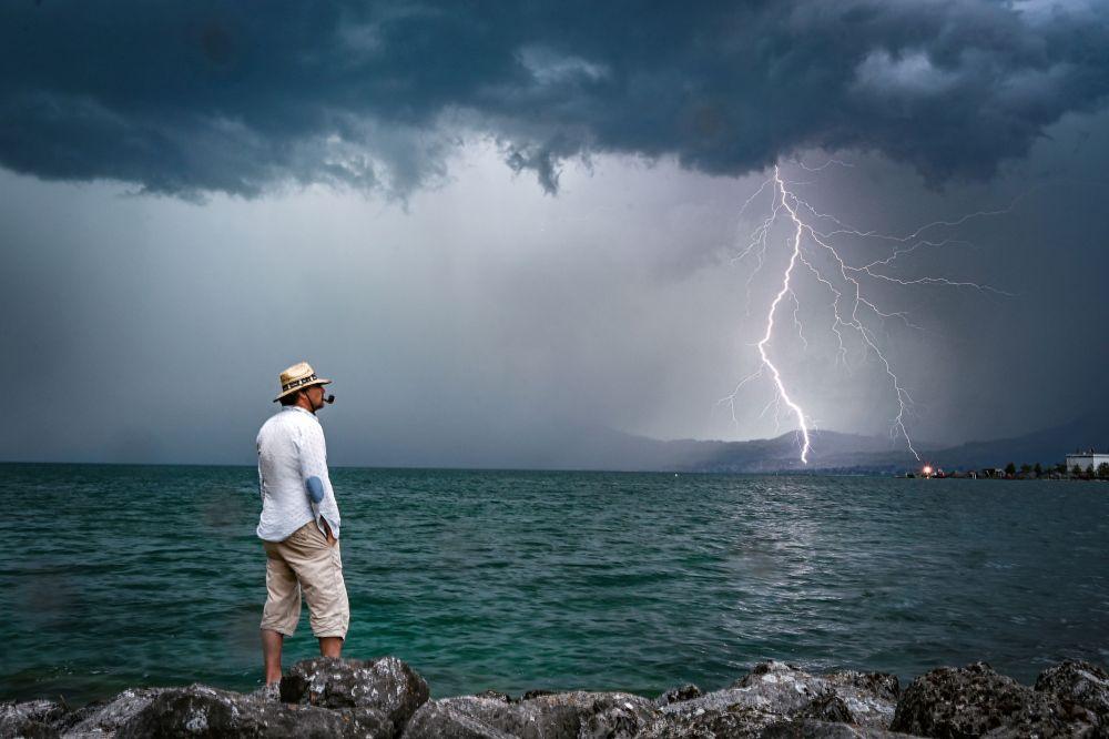 Мужчина наблюдает за грозой на Женевском озере в Швейцарии