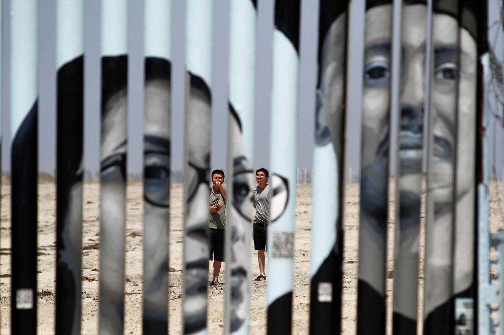 Туристы смотрят на стену, разделяющую Мексику и США, в Тихуане
