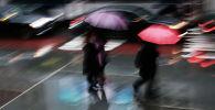 Пешеходы идут по улице во время сильного дождя. Архивное фото