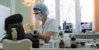 Стоматолог осматривает пациента в городской стоматологической поликлинике. Архивное фото