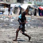 Мальчик уносит своего младшего брата с места столкновений протестующих и полиции в столице Гаити. Полиция применила слезоточивый газ против демонстрантов, вышедших на улицы с требованием отставки президента Жовенеля Моиза.