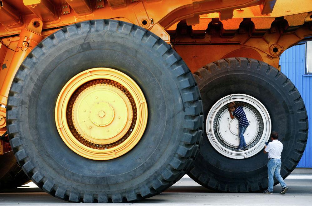 Люди фотографируются у колес самосвала БелАЗ в Белоруссии