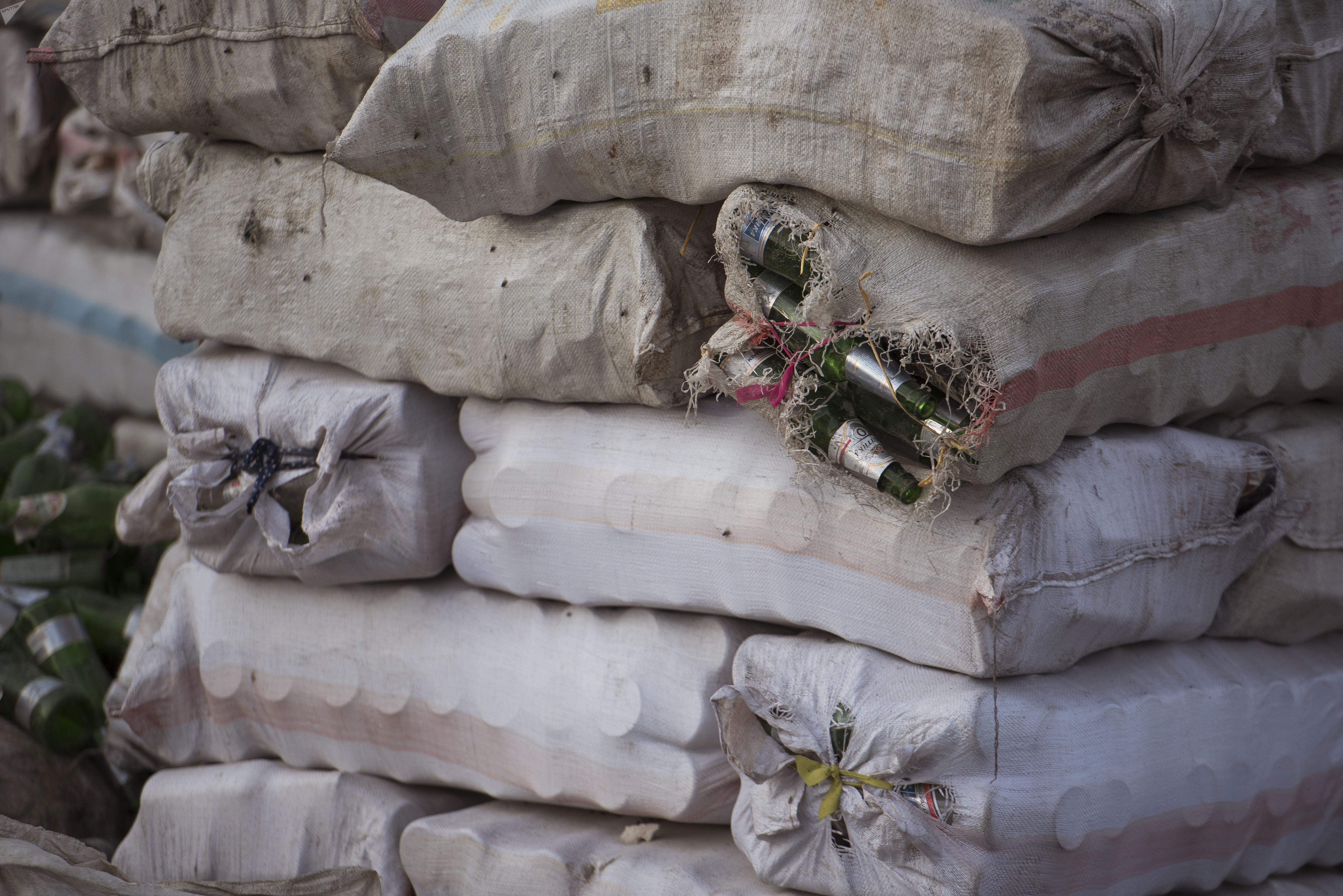 Мешки заполненные, стеклянной тарой на мусорном полигоне близ Бишкека