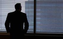 Мужчина стоит у окна. Иллюстративное фото