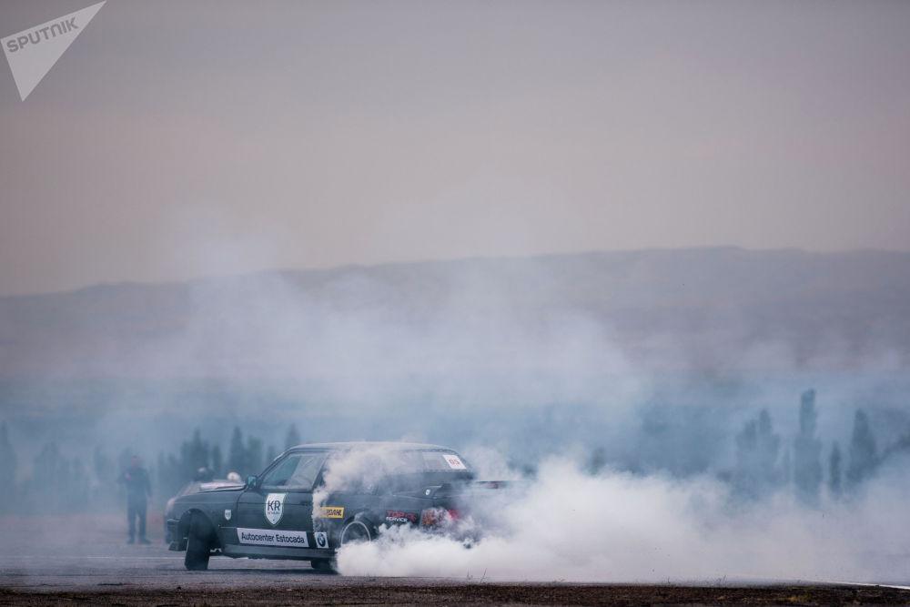 """Дрифттин """"про"""" түрүнө катышкан BMW е-30 спорттук унаасы жолдогу чаңды ызгытып жатат."""
