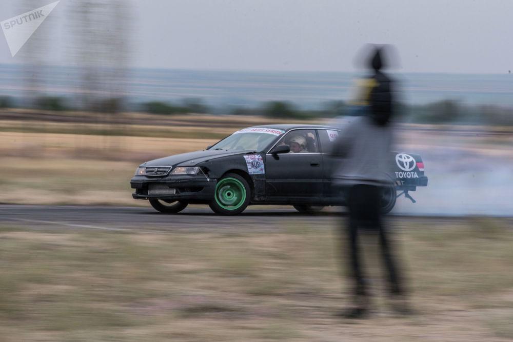 Дагы бир дрифт-такси. Ага жолдомо сатып алган кардар Toyota Mark II унаасынын сол жагында отурат.