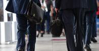 Мужчины в костюмах с портфелями в руках. Архивное фото