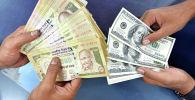 Клиенты пересчитывают рупии и доллары в обменном бюро в индийском городе Бангалор. 24 августа 2013 года