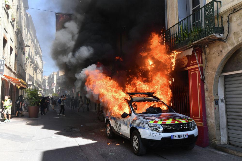 Француз полициясынын өрттөнүп жаткан автоунаасы. Сары күрмөчөндөр Монполье шаарында каршылык акциясын өткөрүштү.