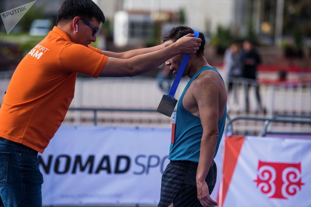 Эстелик медалды тагынып жаткан марафончу