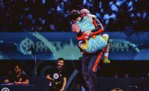 Чемпионка мира Айсулуу Тыныбекова обнимает заслуженного тренера сборной команды КР  по женской борьбе Нурбека Изабекова после финала чемпионата мира по спортивной борьбе в Нур-Султане