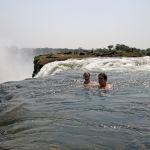Туристы плавают в купели дьявола (Devil's Pool) в Замбии. Природный бассейн находится всего в нескольких метрах от края стометрового обрыва.