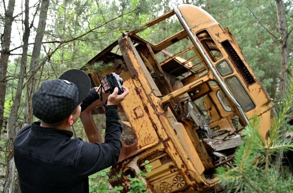 Мужчина фотографирует проржавевший автобус в Припяти во время экскурсии по Чернобыльской зоне отчуждения. Число туристов в зоне значительно выросло после выхода на экраны сериала об аварии на ЧАЭС.