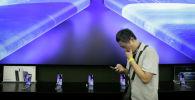 Журналист стоит рядом с плакатом концептуального смартфона Xiaomi Mi MIX Alpha 5G на презентации продукта в Пекине. Китай, 24 сентября 2019 года