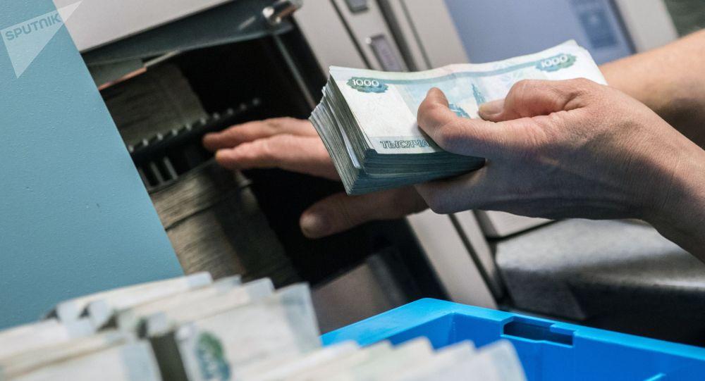 Человек ложит рубли в аппарат. Архивное фото