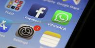 Иконка мессенджера WhatsApp и социальной сети Facebook на экране смартфона. Архивное фото