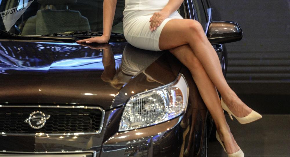 Девушка сидит на капоте авто. Архивное фото