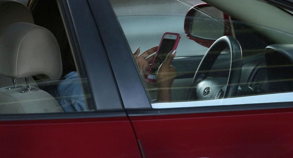 Девушка водитель пользуется телефоном. Архивное фото