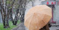 Женщина с зонтом на улице во время снегопада. Архивное фото