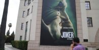 Плакат для предстоящего фильма Джокер можно увидеть у студии Warner Brothers в Бербанке. Калифорния, 27 сентября 2019 года