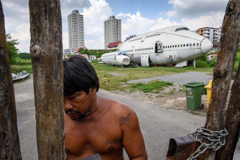 Мужчина берет оплату за вход на кладбище самолетов в пригороде Бангкока