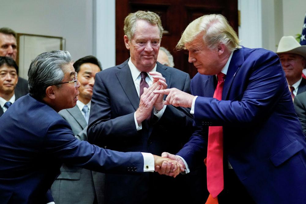 Президент США Дональд Трамп обменивается рукопожатием с послом Японии Шинсукэ Сугиямой во время официальной церемонии подписания в Вашингтоне соглашения о торговле между двумя странами