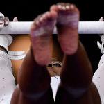 Симона Байлз (США) выполняет упражнения на брусьях в личном многоборье среди женщин на Чемпионате мира по спортивной гимнастике в Штутгарте