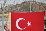 Мужчина-мигрант стоит за забором, украшенным турецким флагом, в лагере беженцев Низип в провинции Газиантеп, юго-восточная Турция. 23 апреля 2016 года