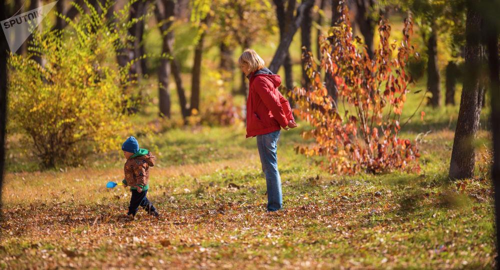 Женщина с сыном гуляют в парке. Архивное фото