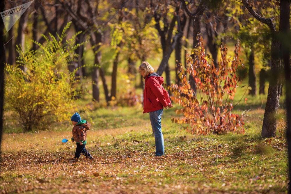 Женщина с сыном гуляют в одном из парков Бишкека