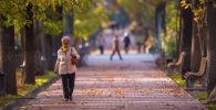 Женщина идет по бульвару Эркиндик в Бишкеке. Архивное фото