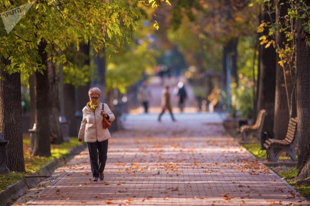 Женщина идет по бульвару Эркиндик в Бишкеке