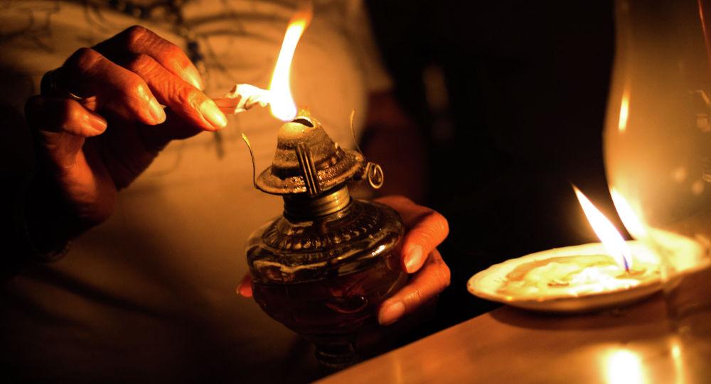 Женщина зажигает керосиновую лампу. Архивное фото