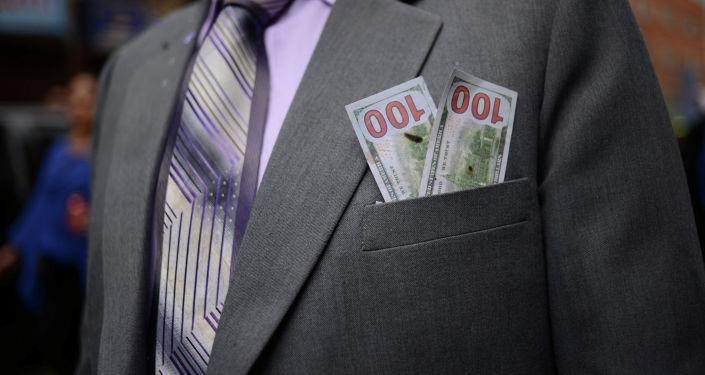 Миниатюрные долларовые купюры в кармане пиджака, символизировающий прошение о богатстве богам во время празднования в преддверии Ла-Паса. Боливия, 28 января 2018 года