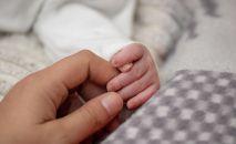 Женщина держит ребенка за руки. Иллюстративное фото