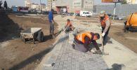 Рабочие укладывают брусчатку и устанавливают бордюры для пешеходной зоны на пересечении улиц Ахунбаева и Тыналиева