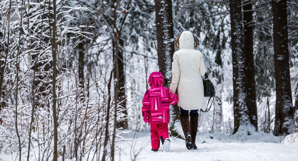 Женщина с ребенком идут в городском парке после снегопада. Архивное фото