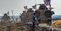 Сирийский мальчик наблюдает за колонной военной техники США патрулирующей недалеко от города Кахтания на границе с Турцией
