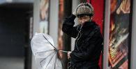 Пешеход держит сломанный зонт, во время сильного ветра. Архивное фото